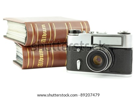 Camera and photo albums isolated on white - stock photo