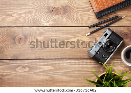 Camera and supplies on office wooden desk table. Top view with copy space - stock photo
