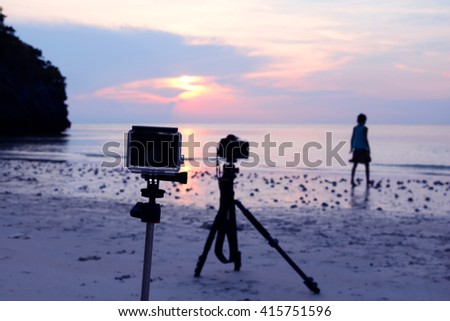 camera and tripod at the beach with a background image of girl with the sunset. - stock photo