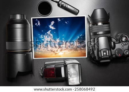 Camera equipment around a printed photo of a sunrise - stock photo