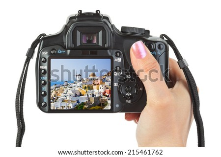 Camera in hand and Santorini view (my photo) isolated on white background - stock photo