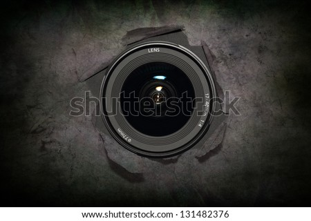 Camera lens hiding behind the paper wall, ready to take a snapsho - stock photo