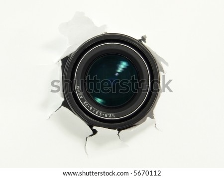 Camera lens hiding behind the paper wall, ready to take a snapshot. Spy concept. - stock photo