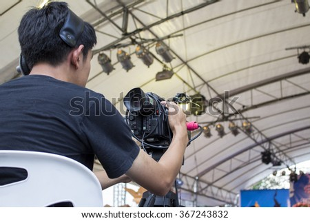 Camera Man shooting video of live concert - stock photo