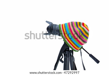 Camera on a tripod and a hat on a white background. - stock photo