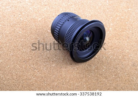 Camera photo lens over brown background - stock photo