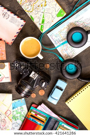 Camera, touristic maps, passport, toy car, coffee, headphones, wallet with credit cards, euro banknotes and coins on a black desk. Travel background. Tourist essentials. Plan a journey. Travel concept - stock photo