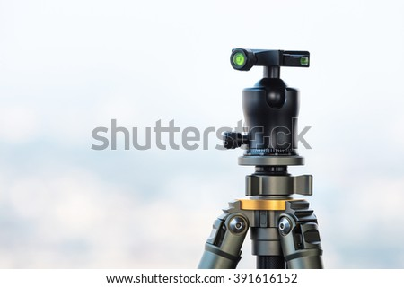 Camera Tripod and Ball head with blur sky in background  - stock photo