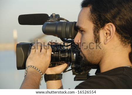 Cameraman Filming Outdoors - stock photo