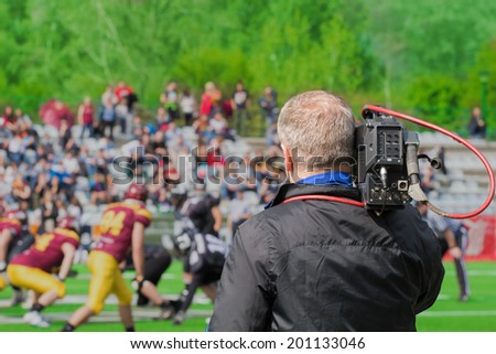 Cameraman shooting an american football game. - stock photo