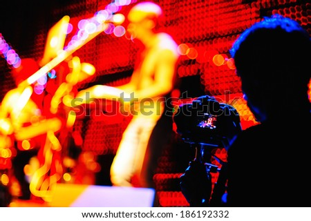 Cameraman silhouette on a concert stage - stock photo