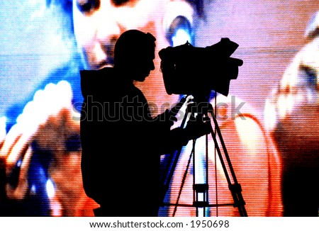 cameraman silhouette on a huge screen - stock photo