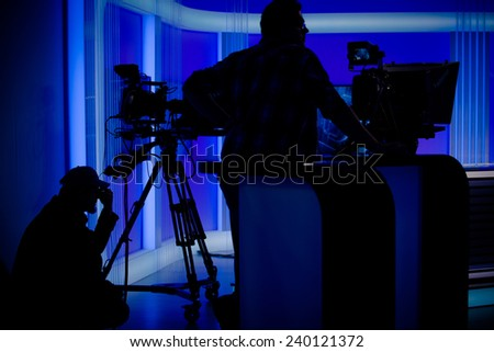 Cameraman silhouettes on a live studio news stage.Professional cameraman with headphones with camcorder in television news broadcast.Camera operators working with big broadcasting cameras - stock photo
