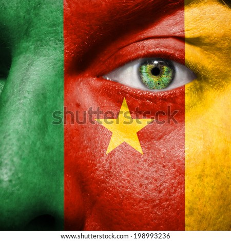 Cameroonian flag painted on a man's face to show support for Cameroon - stock photo