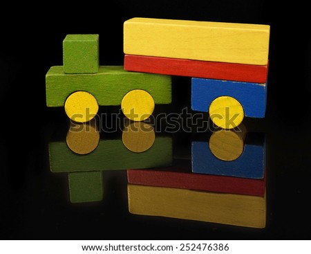 Camion of wooden blocks, traditional toy on black background - stock photo