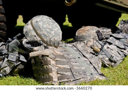 Camouflage combat flak jackets and helmets lined up on the ground - stock photo