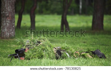 Camouflaged sniper in the field - stock photo