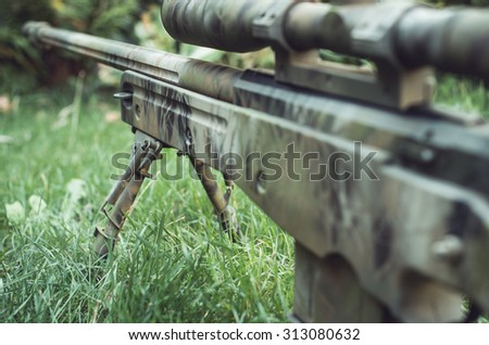 Camouflaged sniper rifle with spotting scope and equipment. Photo edited into warfare look and dark atmosphere. Selective focus. - stock photo