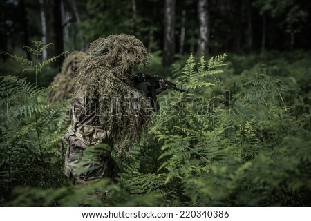 Camouflaged soldier with assault rifle during patrol in forest - stock photo