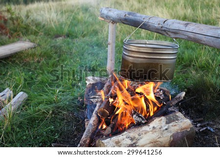 camp fire and preparing food in kettle - stock photo