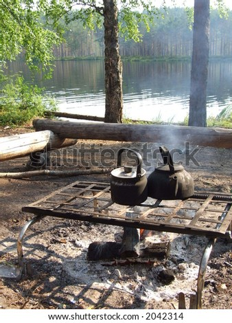 Camp-fire and teapots - stock photo