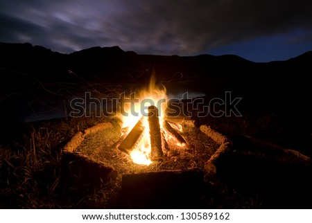 Camp fire beside lake and mountains. - stock photo