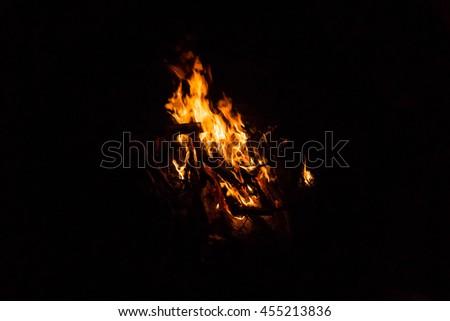 Camp fire burning in the dark night. - stock photo