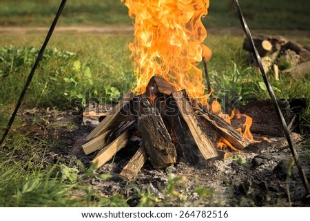 Camp fire outdoors burning with logs closeup  - stock photo