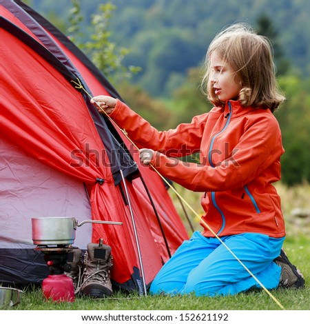 Camp in the tent - young girl setting a tent on the camping - stock photo