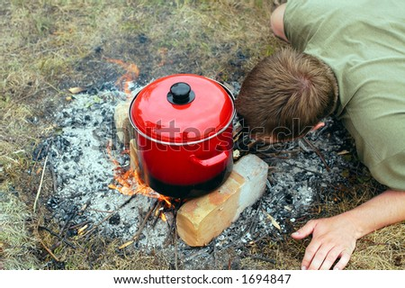 Camp life - blowing on bonfire - stock photo