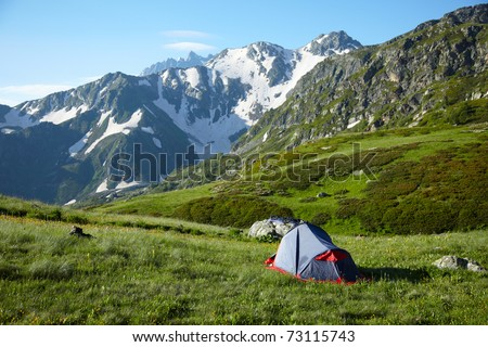 Camp on meadow in the high mountains - stock photo