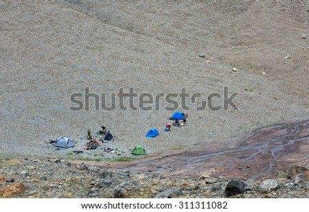Camp on Rocky Moraine. Many camping tents assembled on Rocky Slope along Mountain Creek - stock photo