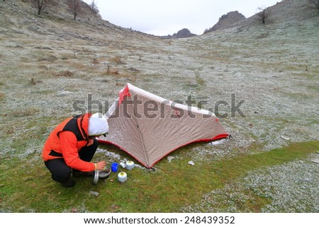 Camper cooks by the tent in cold snowy weather  - stock photo