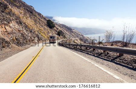 Camper driving the hills of highway one along the Pacific Ocean - stock photo