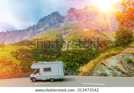 Camper Mountain Trip. Class C Camper Van on a Summer Mountain Road. Camper Journey. - stock photo