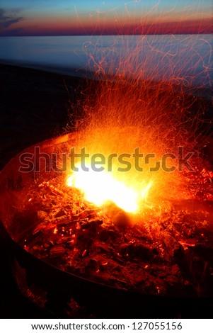 Campfire at sunset along Lake Superior in Michigan - stock photo