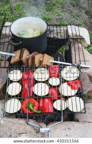 Campfire cooking dinner. Grilled vegetables, toasted bread and hot soup cooking on fire - stock photo