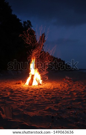 Campfire on the beach in the summer with sparks - stock photo