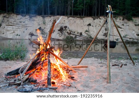 campfire on the beach on the shore of Lake - stock photo