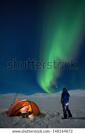 Campground on a Winter expedition with northern lights - stock photo