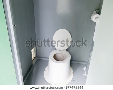 Campground pit toilet outhouse inside white plastic toilet and dirty interior to the toilet bowl with open lid - stock photo