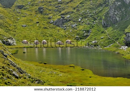 Camping alpine tents near lake - stock photo