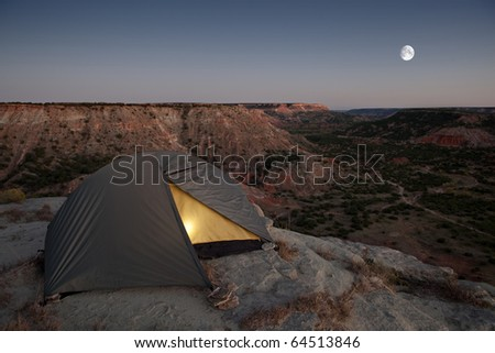 Camping at the Canyon, with light in tent. - stock photo