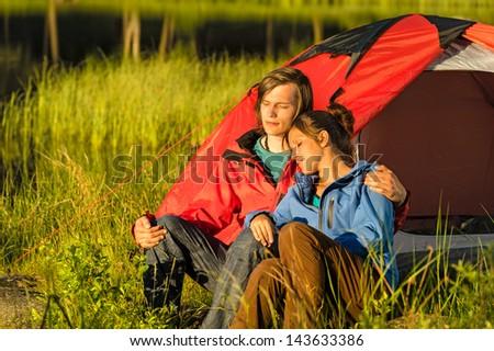 Camping couple hugging and enjoying the sunset - stock photo