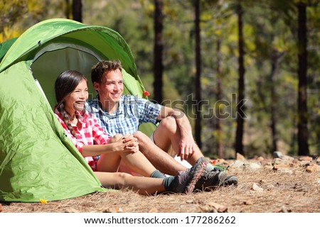Camping couple in tent sitting looking at view in forest. Campers smiling happy outdoors in forest. Happy multiracial couple having fun relaxing after outdoor activity. Asian woman, Caucasian man. - stock photo
