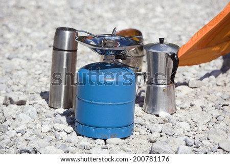 Camping equipment camping stove coffee maker thermos on stony ground - stock photo