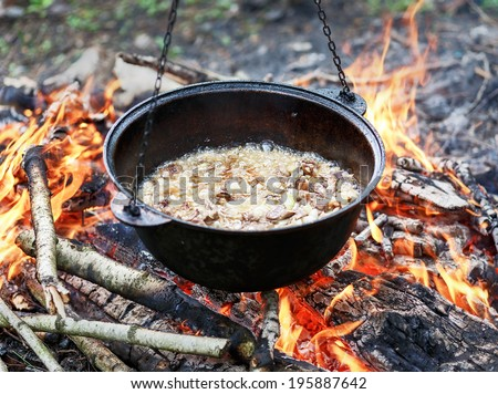 Camping fire and kettle with servak for pilaf - stock photo