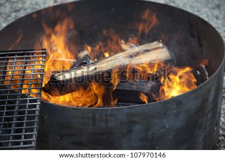 camping fire pit with a wire rack on the side - stock photo