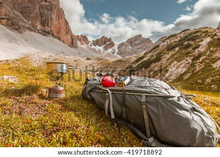 Camping gas, backpack and tourist equipment on Alps background - stock photo