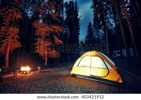 Camping in forest with tent light and bonfire in Banff National Park - stock photo